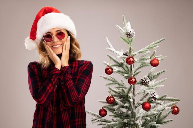 Linda garota sorridente em pé perto da árvore de natal, usando chapéu de natal e óculos cobrindo as bochechas com as mãos isoladas no fundo branco