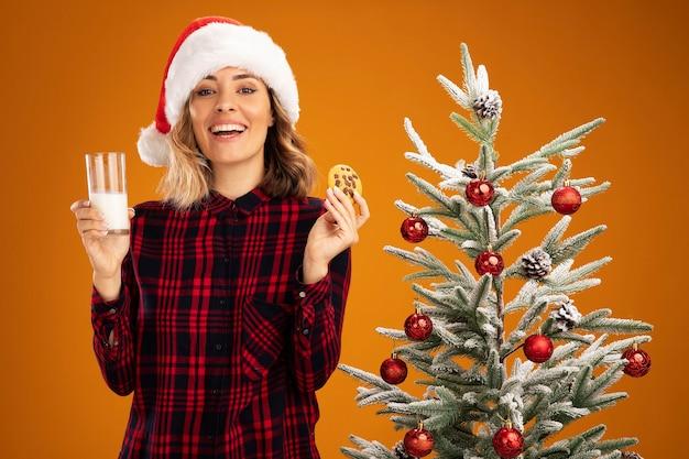 Linda garota sorridente em pé perto da árvore de natal, usando um chapéu de natal, segurando um copo de leite com biscoitos isolados em um fundo laranja