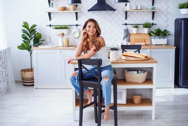 Linda garota sorridente em t-shirt branca senta-se na elegante cozinha branca de manhã.