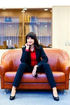 Linda garota sorridente em um terno sentado em um escritório no sofá