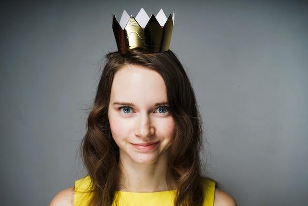 Linda garota sorridente em um vestido amarelo, com uma coroa de ouro na cabeça, esperando o dia mundial da mulher