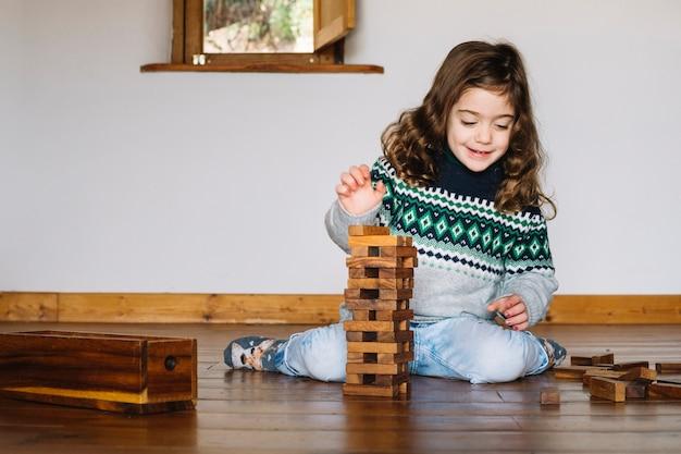Linda garota sorridente, empilhando blocos de madeira