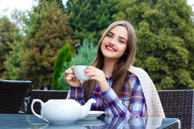 Linda garota sorridente enrolada em um cobertor, segurando uma xícara de chá em um café ao ar livre
