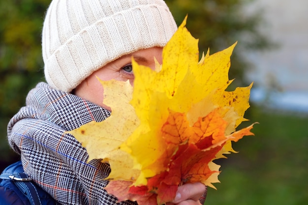 Linda garota sorridente esconde seu rosto atrás de folhas de bordo amarelo-vermelho