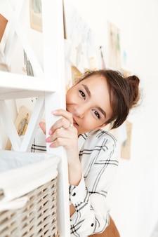 Linda garota sorridente, escondendo-se atrás da estante