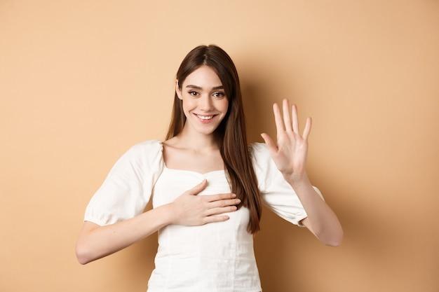 Linda garota sorridente fazer promessa, colocar a mão no coração e dizer a verdade, sendo honesta, jurando para você, de pé sobre um fundo bege.