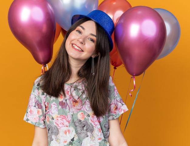 Linda garota sorridente, inclinando a cabeça, usando um chapéu de festa em frente a balões