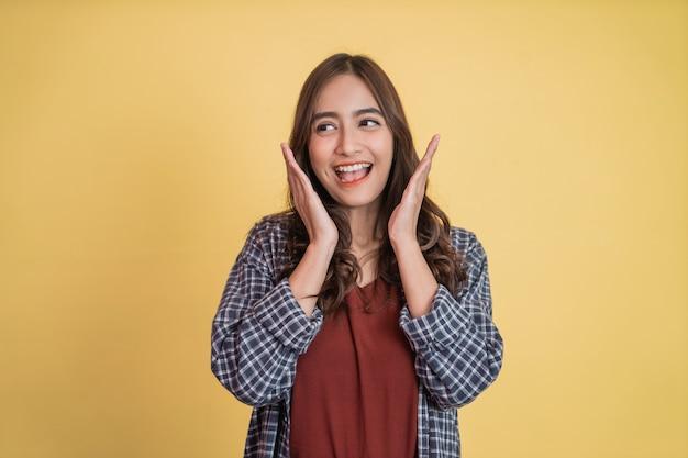 Linda garota sorridente levantando a mão no queixo e sorrindo feliz