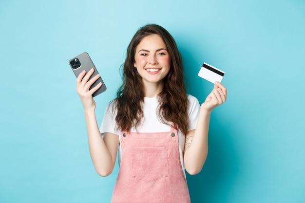 Linda garota sorridente mostrando cartão de crédito de plástico e smartphone, peça algo na loja via aplicativo móvel, compre online ou pague o pedido, em pé contra um fundo azul