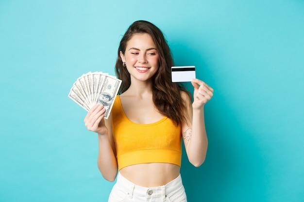 Linda garota sorridente mostrando dinheiro, mas olhando para o cartão de crédito de plástico com cara determinada e satisfeita, de pé sobre um fundo azul.
