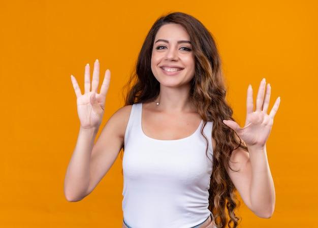 Linda garota sorridente mostrando quatro e cinco em um espaço laranja isolado
