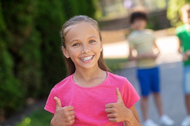 Linda garota sorridente mostrando um gesto de ok