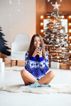 Linda garota sorridente na camisola quente do ano novo senta-se em um tapete branco quente