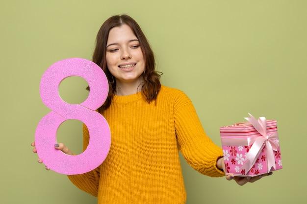 Linda garota sorridente no feliz dia da mulher segurando o número oito, olhando para o presente na mão