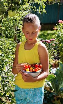 Linda garota sorridente no jardim coletando