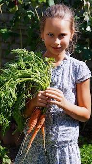 Linda garota sorridente no jardim com cenouras cruas frescas
