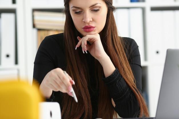 Linda garota sorridente no local de trabalho segurar caneta prata