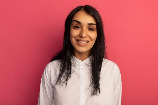 Linda garota sorridente olhando para a frente usando uma camiseta branca isolada em rosa