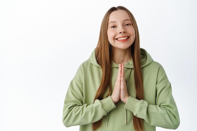 Linda garota sorridente, pedindo favor com um sorriso, implorando muito, por favor, pareça grata e esperançosa, em pé sobre uma parede branca.