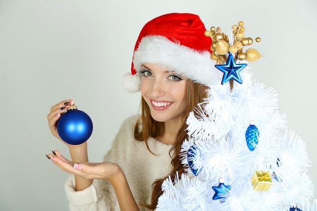 Linda garota sorridente perto da árvore de natal com uma bola