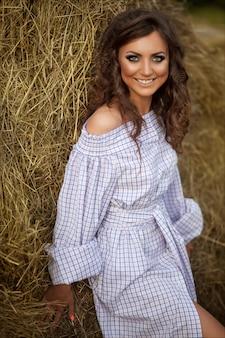Linda garota sorridente perto de um fardo de feno na zona rural