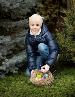 Linda garota sorridente recolhendo ovos de páscoa no quintal