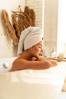 Linda garota sorridente relaxando deitado na banheira no banheiro. em sua toalha branca de cabeça. conceito de cuidado e beleza em casa