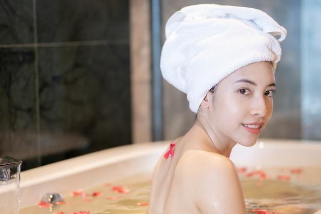 Linda garota sorridente relaxante no banho com pétalas de rosa.