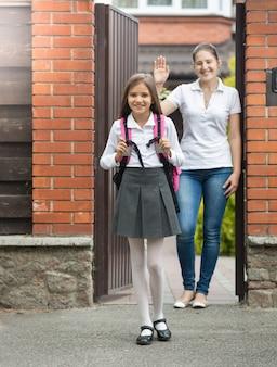 Linda garota sorridente, saindo de casa para a escola. mãe parada na porta e acenando para ela