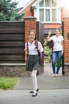 Linda garota sorridente saindo do quintal de casa para a escola