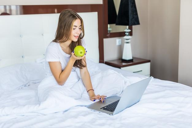 Linda garota sorridente se senta na cama de manhã cedo, come uma maçã e sorri, com um laptop