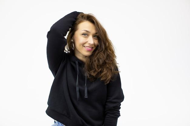 Linda garota sorridente segura a mão no cabelo encaracolado com capuz preto aguarda com expectativa