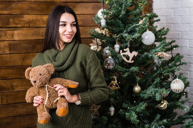 Linda garota sorridente segura um ursinho de pelúcia nas mãos.