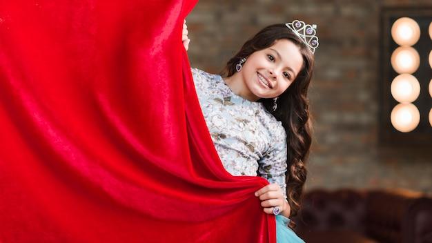 Linda garota sorridente segurando a cortina vermelha