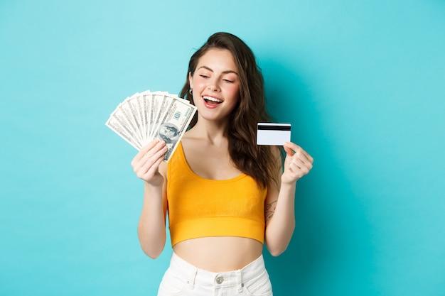 Linda garota sorridente, segurando o cartão de crédito, parecendo satisfeita e determinada com o dinheiro das notas de dólar, de pé contra um fundo azul.