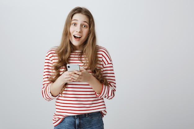 Linda garota sorridente segurando um smartphone e parecendo satisfeita
