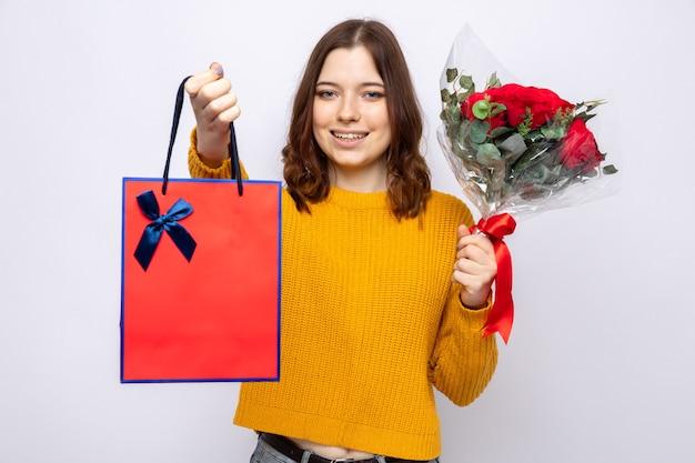 Linda garota sorridente segurando uma sacola de presente com buquê