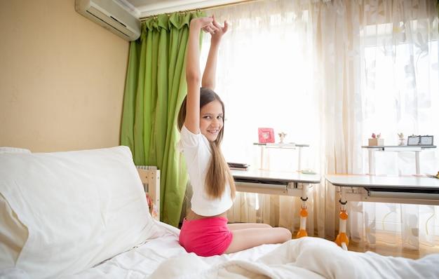 Linda garota sorridente sentada ao lado da cama e esticando as mãos na manhã ensolarada