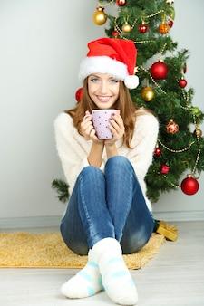 Linda garota sorridente sentada perto da árvore de natal com uma xícara