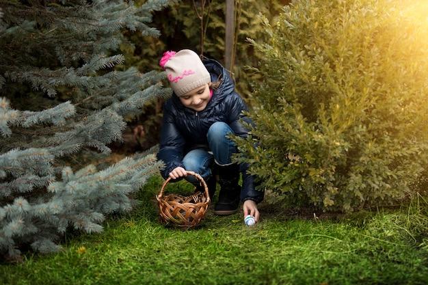 Linda garota sorridente tomando forma de ovo de páscoa sob o arbusto em um quintal
