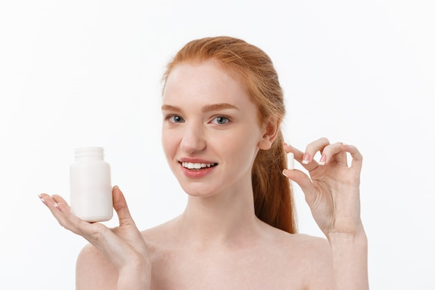 Linda garota sorridente tomando medicação, segurando a garrafa com comprimidos. mulher feliz e saudável comer pílula. vitaminas e suplementos, conceito de nutrição dietética