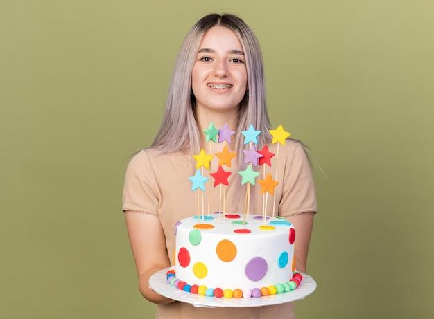 Linda garota sorridente usando aparelho dentário e segurando um bolo para a câmera
