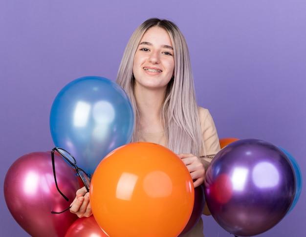 Linda garota sorridente usando aparelho dentário em pé atrás de balões segurando óculos isolados na parede azul