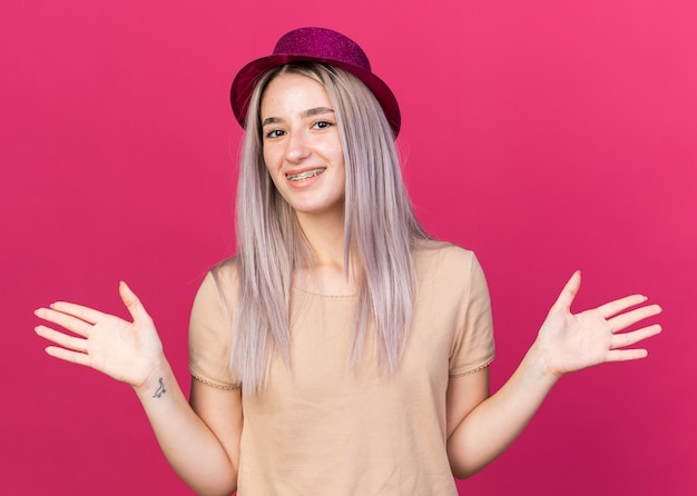 Linda garota sorridente usando chapéu de festa com aparelho dentário estendendo as mãos