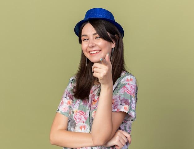 Linda garota sorridente usando chapéu de festa mostrando seu gesto