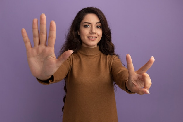 Linda garota sorridente usando um suéter de gola alta marrom mostrando diferentes números isolados na parede roxa