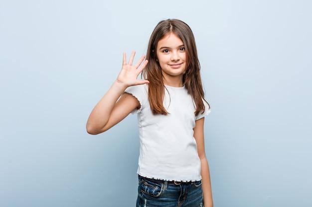 Linda garota sorrindo alegre mostrando número cinco com os dedos