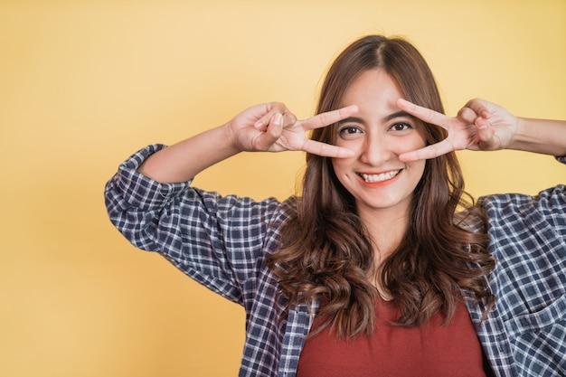 Linda garota sorrindo com paz fazendo gestos com as duas mãos na frente dos olhos