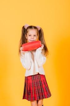 Linda garota sorrindo e dançando com alto-falante portátil sem fio no fundo amarelo do estúdio. humor de ano novo.