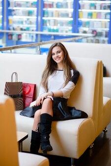 Linda garota sorrindo e fazendo compras no shopping.